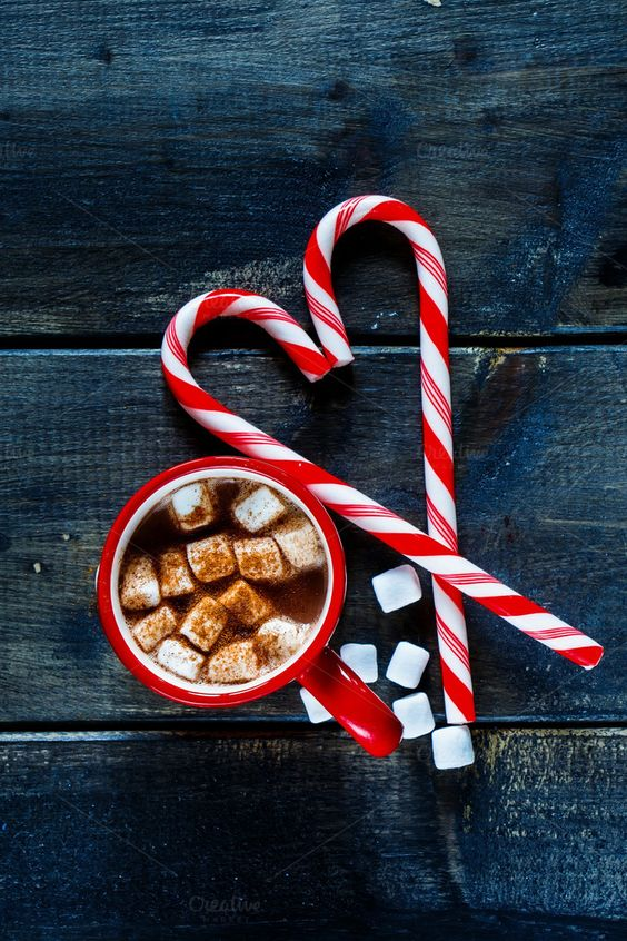 #Traditional hot chocolate  Top view of traditional hot chocolate with marshmallows and candy sticks over dark texture background. Christmas drink theme.