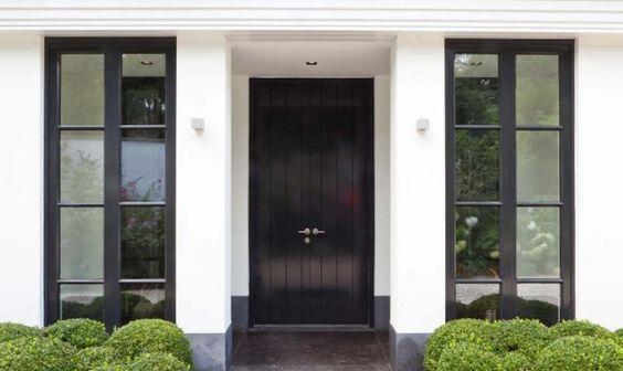 Luxe tijdloze uitstraling bij een wit pand, donkere raamkozijnen en een donkere voordeur. Deze willen we