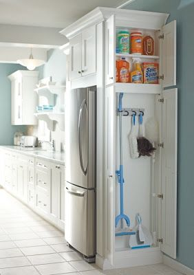 Broom closet cleverly hidden on the side of a refrigerator cabinet.  So clever so handy.