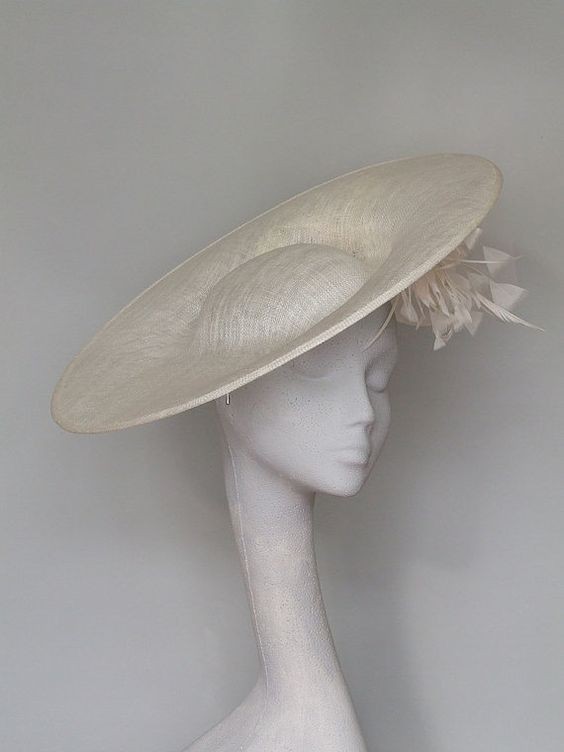 Ivory sinamay disc headpiece, trimmed with feathers, crin and sinamay curls.  Stunning and feminine, this hat is perfect for all special occasions, ideal for a wedding or a day at the races.  Sits securely on a satin headband.    Please allow 5 business days for this item to be made  Shipment to USA by courier.