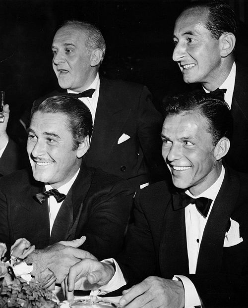 Errol Flynn and Frank Sinatra at a party at the Mocambo, with Walter Winchell and Leonard Lyons (1947)