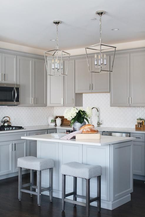Two Backless Gray Linen Saddleback Stools Sit At A White Quartz Countertop Quartz Kitchen Countertops White Interior Design Kitchen Small Grey Kitchen Cabinets