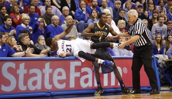 Kansas center Joel Embiid and Toledo guard Justin Drummond wrestle on the press table during the second half on Monday, Dec. 30, 2013 at Allen Fieldhouse. #KU