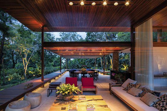 Nesta casa telhas, muros de pedra, venezianas e estrutura em madeira convivem com grandes portas de vidro, beirais largos e cômodos em balanço.