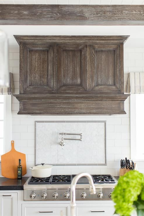 A Dark Stained Wood Vent Hood Is Fixed To White Subway Backsplash Tiles Between Windows And Above A Trendy Farmhouse Kitchen Farmhouse Kitchen Backsplash Home