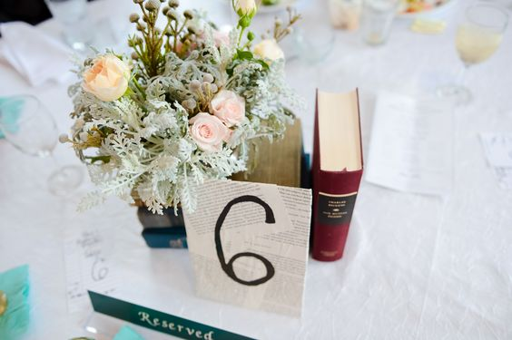 Wedding centerpiece: Gorgeous flowers, vintage book, and book-pages table number card.  I'm pretty proud of this, actually. #LibraryWedding