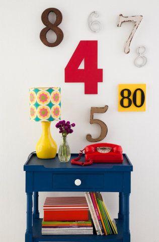 Dessa vez, são os números que compõem o arranjo de parede. Números da C&C e Raízes Design. O móvel é da Armazém e o telefone da Minha Avó Tinha. A luminária e a cúpula com tecido são da Tantum.