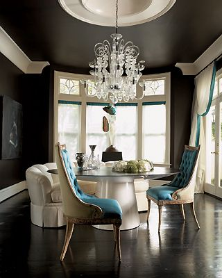 Dramatic black & turquoise blue dining room design with black painted walls and large crystal chandelier! Love the upholstered turquoise tufted chairs and glossy white round lacquer dining room table. Black dining room. Black paint wall color! so gorg