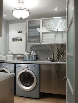 Sarah Richardson Design.    Snazzy, modern white & blue laundry room design with metal backsplash? Is it aluminum? Love the retro modern pendant light and frosted glass front cabinets! Blue gray silver laundry room colors.