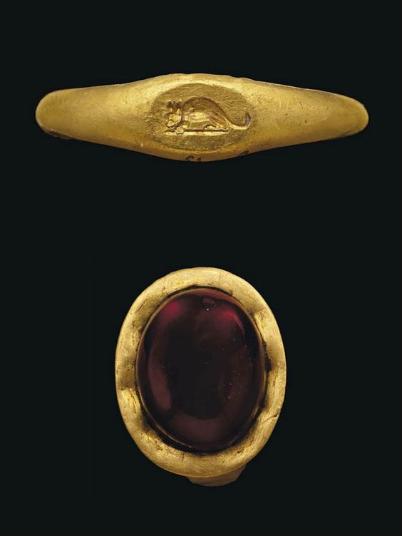 FOUR SMALL ROMAN GOLD RINGS   CIRCA 1ST CENTURY B.C.-2ND CENTURY A.D.   One with plain hoop widening to an oval bezel with applied phallus; another with bezel with incised figure of a mouse, both circa 2nd Century A.D.; another with high banded bezel with pale green glass inlay; and another with flat hoop, oval bezel with later cabochon garnet, both circa 1st Century B.C.- 1st Century A.D.  5/8 in. (1.5 cm.) wide max.