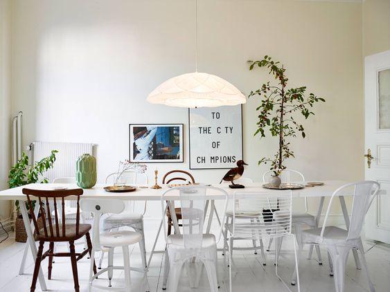 Suspension basse sur la table à manger + chaises dépareillées + plantes vertes: