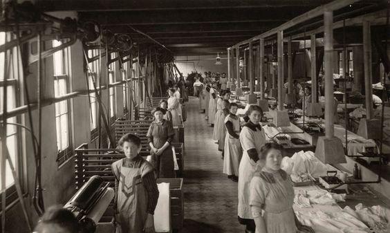 En lange rij vrouwen en meisjes op de stoom - en strijkafdeling van wasserij Burger. Ze dragen lange bedrijfskleding. De strijkbouten worden verwarmd op [gas]comfoortjes. Zeist, 1915.