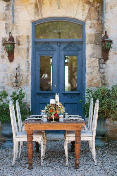 French farmhouse courtyard dining area with blue doors and farm table. #frenchfarmhouse #europeanfarmhouse #courtyard #rustic #dining