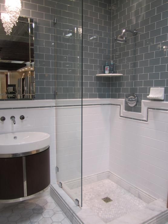 grey glass tile, white subway tile and large marble hex on floor.