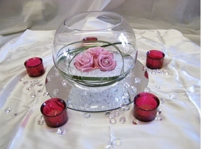 We have mirror and votive candles free from the reception site.  We can order blue stones, line the bottom of the fish bowl, fill with some water, and float a white flower (fake or real).