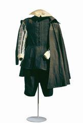 Jubón, ropilla y calzón de terciopelo negros, medias negras de punto de seda, herreruelo, cuello de golilla, y valona blanca.  Confeccionado en 1655 por un sastre español, conforme a las normas de la etiqueta de la Corte española.