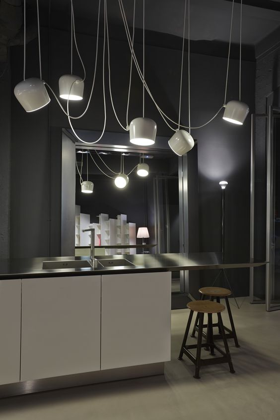 Ronan and Erwan Bouroullec's AIM modern pendant lights for FLOS add a modern element to this spacious, chic interior with deep purple accents.