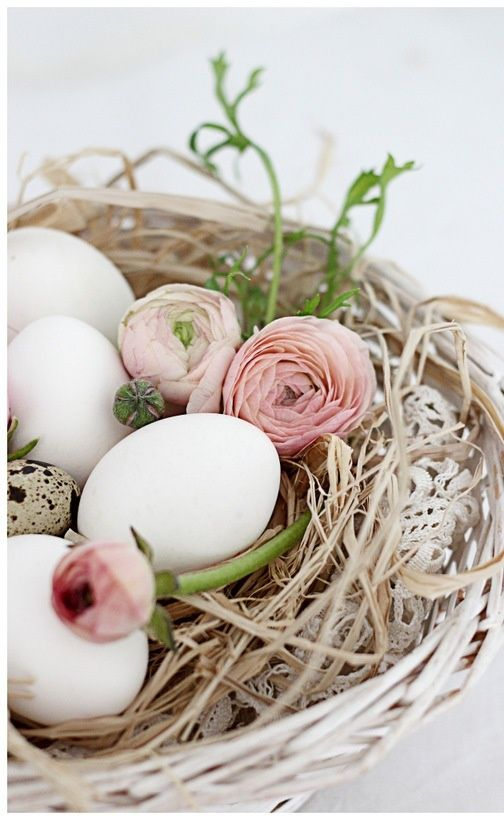 Interesting arrangement concept: a nest with eggs and fresh flowers:
