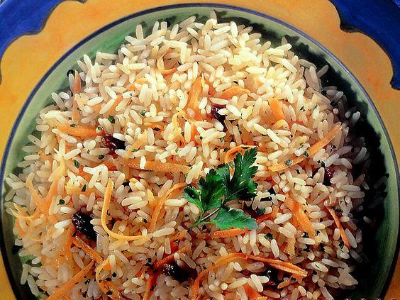 ARROZ DO REI. - 2 cubos de caldo de legumes; - 2 xícaras (chá) de arroz lavado e seco; - 1 colher (sopa) de manteiga; - 2 cenouras raladas; - 150 g de uvas-passas pretas sem sementes; - 2 colheres (sopa) de salsinha picada.    1 - Derreta os cubos de caldo de legumes em fogo