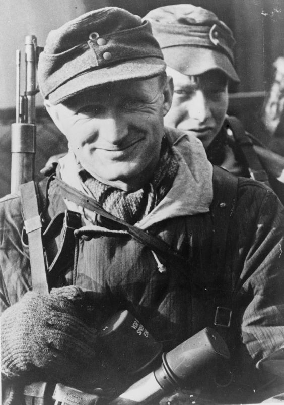 """Portrait of an unknown German Grenadier in defensive positions at the river Oder, Germany, 1945. This middle aged German has the courage to smile; not so the youngster right behind him. Note the high quality clothing, quite an achievement at this stage in the war, and the two """"potato masher"""" hand grenades stuck in the belt of the smiling man."""