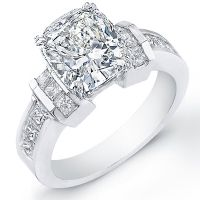 A fascinating diamond ring that will bring years of memories. This dazzling engagement ring contains a 1.25 Ct. Cushion Cut diamond with a color of H and clarity of VS1. Sparkling Princess Cut diamond having a total carat weight of 0.77 Ct. compliments the side and flows down the shank. The color and clarity of the side stones will be matched with the color and clarity of the center stone. The total weight of this beautiful engagement ring is 2.02 Ct. made in 14k white or yellow gold but is…
