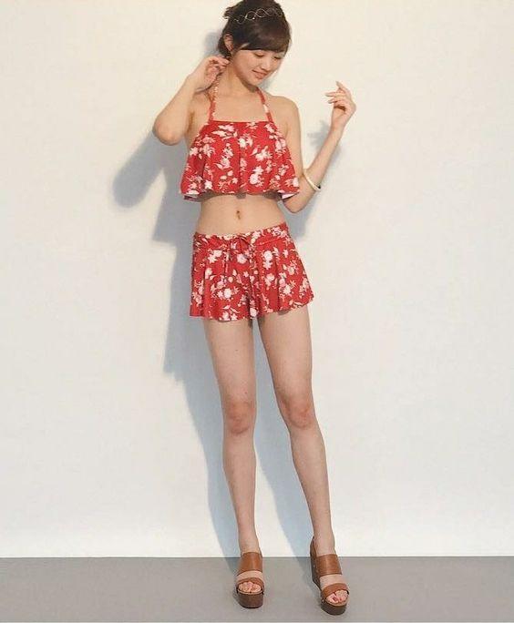 赤い花柄のフリルのビキニを着て立っている熊江琉唯の画像