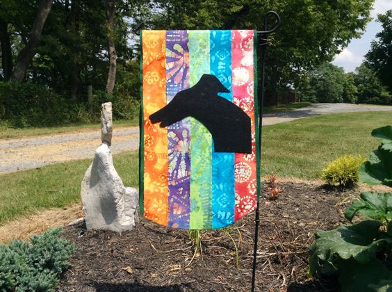Small garden flag made from felt and fabric scrapes.