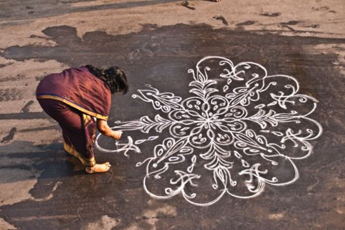 Kolam is a form of sand painting that is drawn using rice powder by female members of the family in front of their home. It is widely practiced by Hindus in South India. A kolam is a sort of painted prayer - a line drawing composed of curved loops, drawn around a grid pattern of dots. Kolams are thought to bestow prosperity to homes.: Line Drawings, Chalk Drawing, Rice Powder, Floor Design, Rangoli Design, South India, Painted Prayer