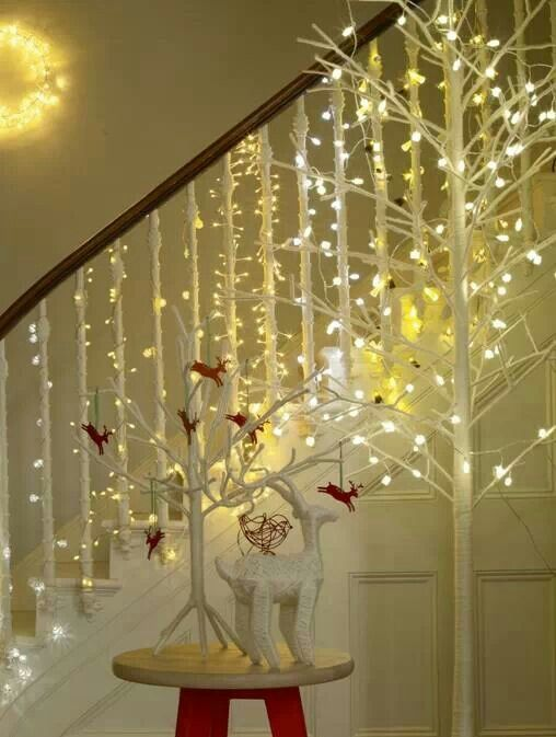 Christmas lights wrapped around each stair railing for How to decorate a banister