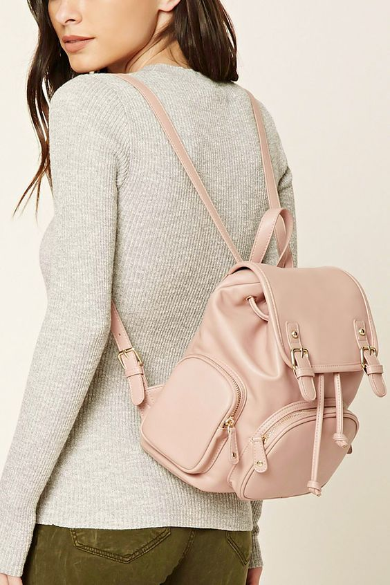 An unstructured faux leather backpack featuring a drawstring closure, flap top with high-polish buckles and a snap-button, top handle, adjustable shoulder straps, front zippered pocket, two side zippered pockets, an interior zippered pocket, and two interior slit pockets.