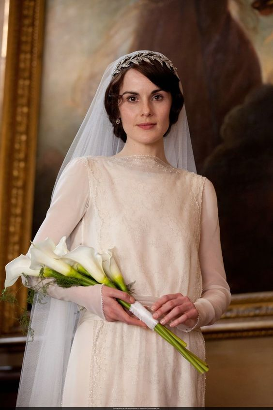 Ah, the royals!  Lady Mary carried a simple bouquet of several long-stemmed white Calla lilies with greenery, tied together with white ribbon and pearl-headed pins. Any florist should be able to create a similar arrangement for you, and DIY brides can also put it together quite easily the morning of their wedding.