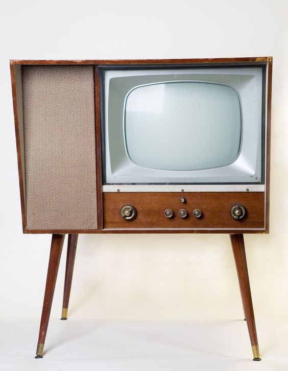 There are several clues that this television is outdated. This most obvious would have to be it's shape. The tv is rectangular like television sets today but it has four legs connected to it. Also the screen is very small and put on to the top right hand corner. It is also dated by the nobs on the bottom instead of having buttons. It is also dated by its brown color. Also it is much wider then the flat screen television sets of today. It is primarily outdated in it's form.: