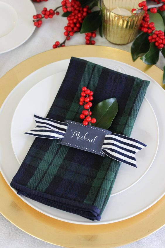 A festive holiday place setting with black watch plaid napkins, striped ribbon and red ilex berries.