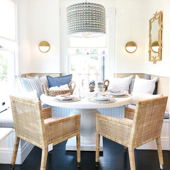Beautiful kitchen dining area | breakfast nook with woven cane dining chairs, round white pedestal table and banquette with pillows #kitchen #dining #nook