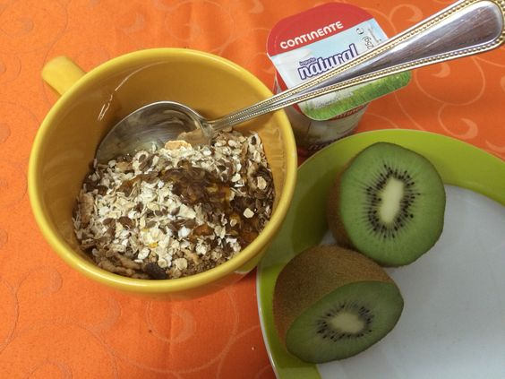 Um pequeno-almoço: cereais, aveia, iogurte natural, um kiwi