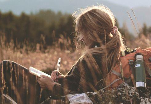 Mujer escribiendo en el campo: