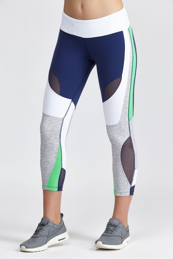 Lightly tanned lady in color block yoga pants (indigo, snow, graphit, heather grey, & mint), cream-soled graphite shoes