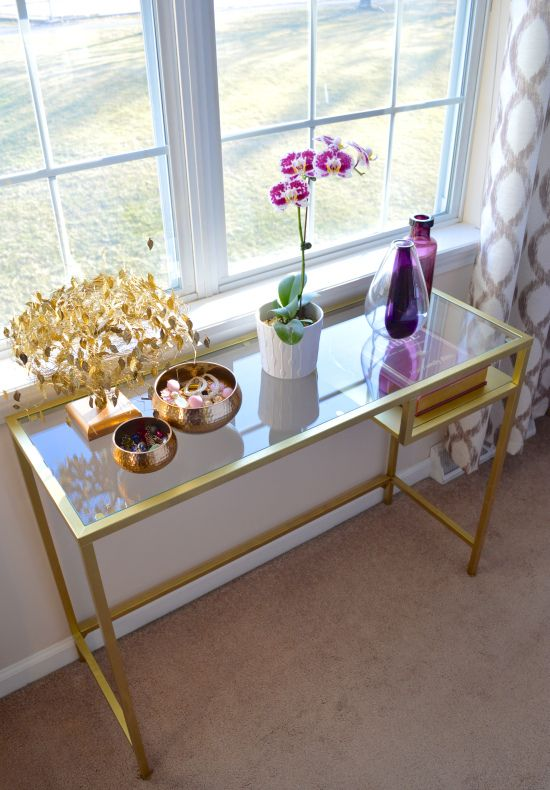 Gold console table under the double windows: