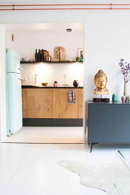 Blauwe Smeg, houten keukenkastjes, witte metrotegel, zwarte plint. Accenten in koper. eclectic kitchen by Louise de Miranda