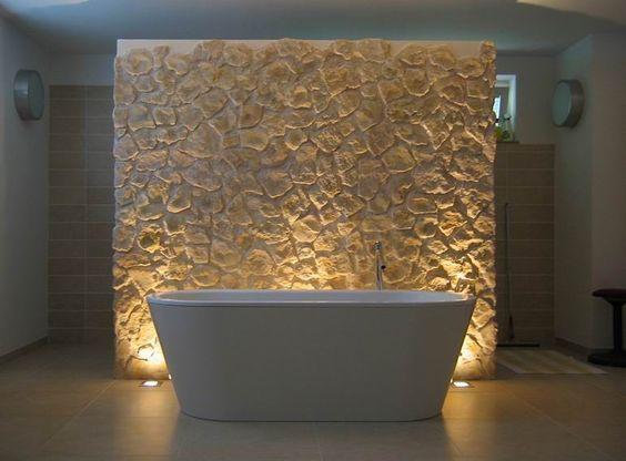 Badezimmer mit Badewanne und Rückwand aus Stein ...