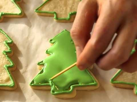This video tutorial shows decorating tips for turning plain cookies into beautiful Christmas tree cookies. See how to decorate Christmas tree cookies at home and make them look like they were done by a professional.