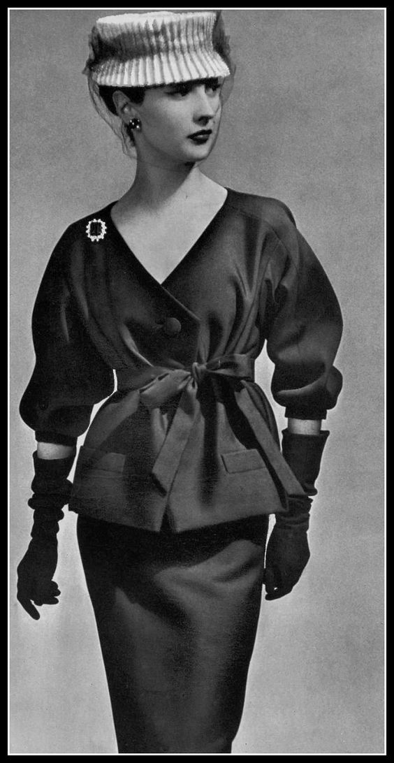 Renée Breton in navy blue alpaca two-piece, top tied with same-fabric belt, white toque with navy voilette, by Christian Dior, photo by Georges Saad, 1956. Image via Pinterest.