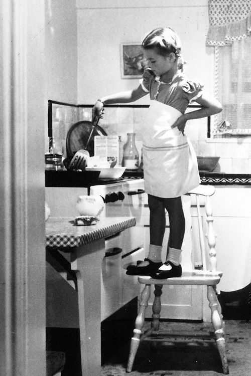 6 year-old Natalie Wood helping her mother in the kitchen, photographed by Martha Holmes, 1944.: