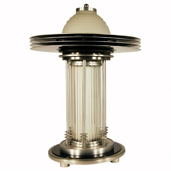 This stunning Art Deco style table lamp features a domed glass shade encircled by four anodized aluminum rings and held up by six aluminum poles. 1990s