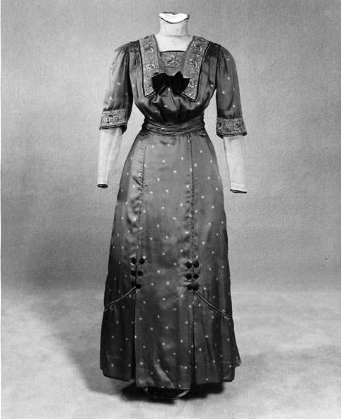 Copenhagen blue printed silk dress, North Carolina, 1910. Bloused bodice rimmed with multi-colored floral embroidered net and rose & black piping. Lace on yoke and lower sleeves. Cummerbund. North Carolina Museum of History