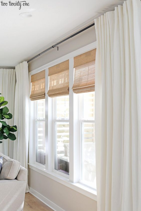 Living room window treatments featuring budget-friendly cordless woven shades and linen cotton curtains, paired with black curtain rods. #livingroom