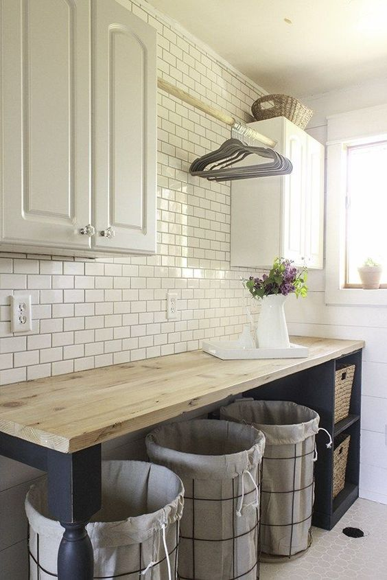 Laundry is less of a chore in this gorgeous farmhouse makeover. Shiplap walls, subway tile, reclaimed butcher block counter tops, turned table legs, and farmhouse sink have this laundry room oozing farmhouse charm.