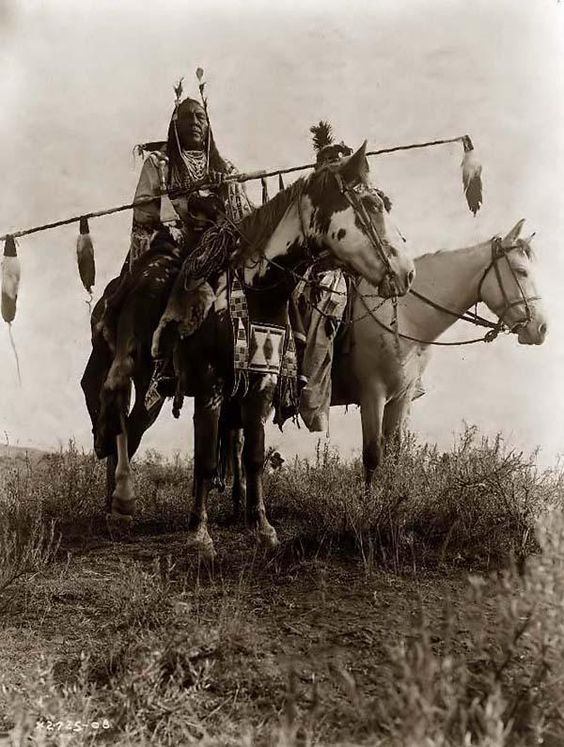 You are viewing an important image of Crow Warriors On Horseback. It was taken in 1908 by Edward S. Curtis.    The picture shows Bird on the Ground and Forked Iron dressed in Traditional Native American style.    We have created this collection of pictures primarily to serve as an easy to access educational tool. Contact curator@old-picture.com.    Image ID# 216B17E7: