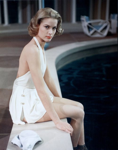 Grace Kelly, 1950s, lounging by a pool with perfect hair and makeup, Kelly is photo-ready in a white frock and matching bikini bottoms.:
