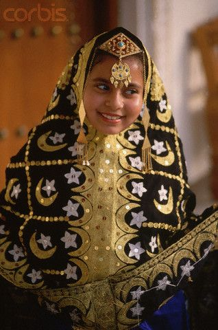 A woman wears a traditional costume of robe and headdress at the Heritage Center in Bahrain. | © Adam Woolfitt/Corbis